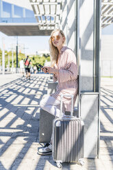 Spain, Barcelona, young woman with trolley bag and cell phone waiting at station - GIOF05468