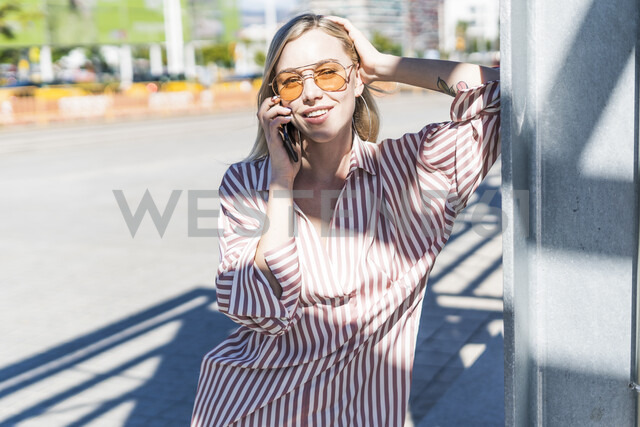 Portrait of blond young woman on the phone outdoors - GIOF05471