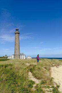Denmark, Jutland, Skagen, Grenen, woman standing in dunes at grey lighthouse - UMF00897