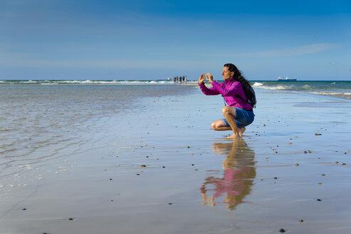Denmark, Jutland, Skagen, Grenen, woman taking pictures of North Sea and Baltic Sea - UMF00903