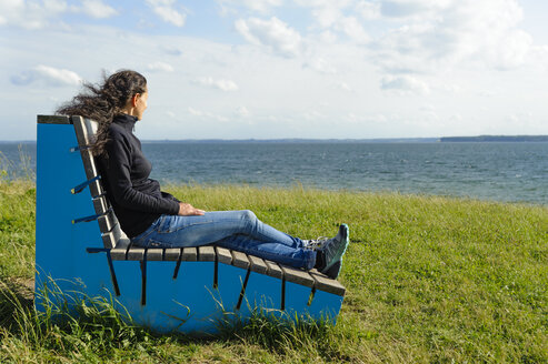 Denmark, Jutland, Sonderborg, woman sitting on park bench at Sonderborg bay - UMF00921