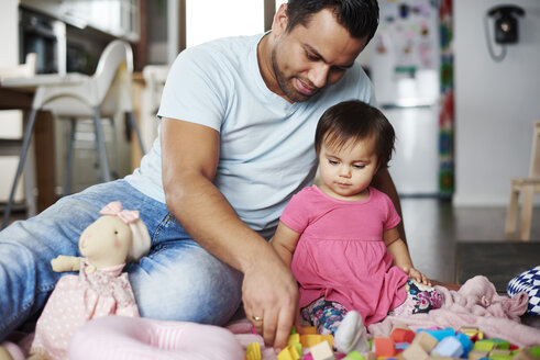 Father and baby girl playing with building blocks at home - ABIF01080