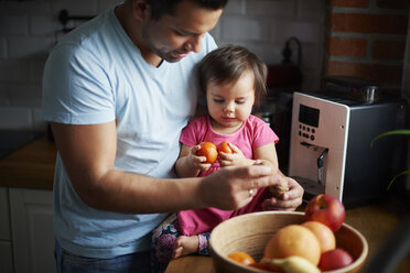 Father and baby girl eating fruit in kitchen at home - ABIF01089