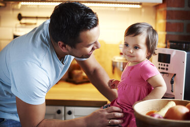 Smiling father looking at baby girl sitting on counter in kitchen at home - ABIF01095