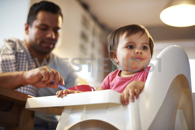 Portrait of baby girl sitting in high chair at home with father in background - ABIF01098 - gpointstudio/Westend61