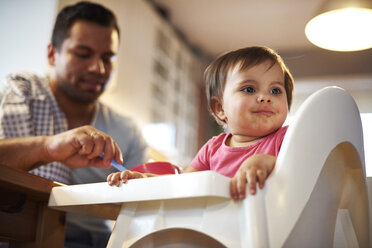 Portrait of baby girl sitting in high chair at home with father in background - ABIF01098