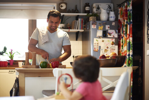 Smiling father preparing food for his daughter in kitchen at home - ABIF01101