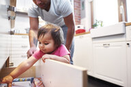 Baby girl helping father in kitchen at home - ABIF01104