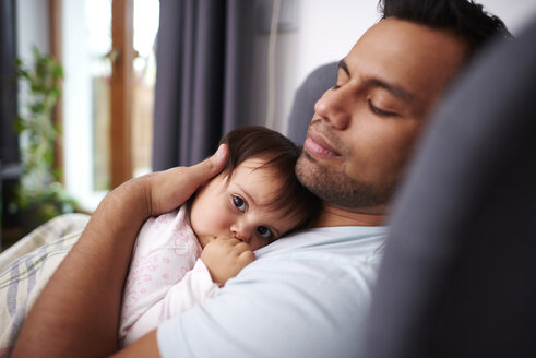 Affectionate father hugging his baby daughter at home - ABIF01107
