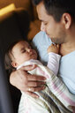 Affectionate father looking at baby girl sleeping in his arms - ABIF01110