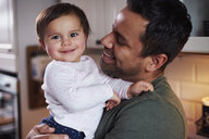 Portrait of smiling father holding baby girl at home - ABIF01116