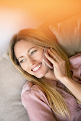 Portrait of woman on the phone relaxing on couch at home - DMOF00085