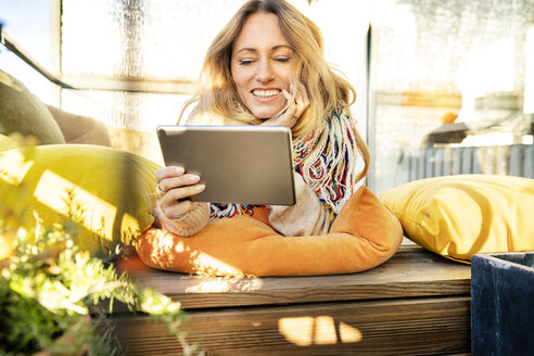 Portrait of smiling blond mature woman relaxing in winter garden using digital tablet - DMOF00094