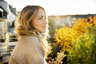 Blond mature woman enjoying sunny autumnal day on balcony - DMOF00100