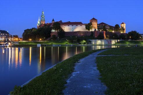 Poland, Krakow, Wawel Royal Castle at dusk, historic city landmark, alley along the Vistula River - ABOF00381