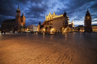 Poland, Krakow, Main Square in the Old Town at evening twilight with St Mary's Church, Cloth Hall and Town Hall Tower - ABOF00393