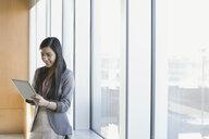 Businesswoman using digital tablet at office window - HEROF04181