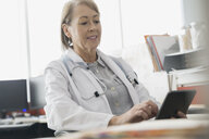 Doctor using digital tablet in office - HEROF04187