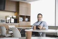 Doctor using digital tablet in break room - HEROF04274