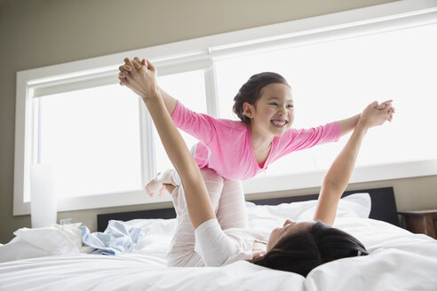 Mother and daughter playing on bed - HEROF04442