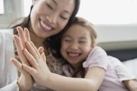 Mother and daughter touching hands - HEROF04445
