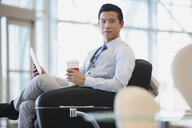 Portrait of businessman with digital tablet and coffee - HEROF04457