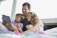 Father and daughters using digital tablet on bed - HEROF04559