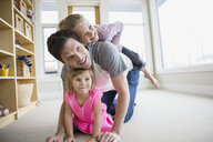Father and daughters playing in living room - HEROF04601