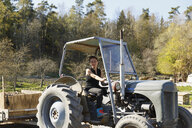 Mid adult woman on tractor in Sweden - FOLF09704
