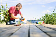 Mid adult man sawing a deck in Finland - FOLF09830