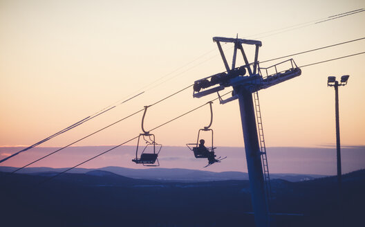 A person riding a ski lift at sunset in Pyha, Sweden - FOLF09875