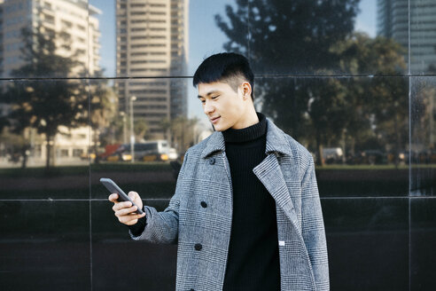Spain, Barcelona, young man wearing black turtleneck pullover and grey coat looking at cell phone - JRFF02445