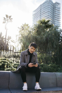 Spain, Barcelona, portrait of young man with mobile phone sitting on a wall - JRFF02448