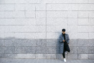 Young man leaning against wall looking at mobile phone - JRFF02460
