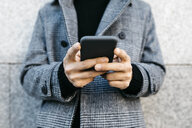 Man's hands holding smartphone, close-up - JRFF02463