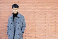 Portrait of young man wearing grey coat - JRFF02472