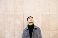 Young man wearing turtleneck pullover and coat looking up - JRFF02475