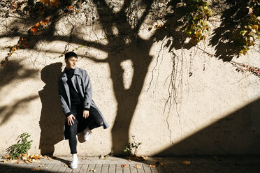 Relaxed young man leaning against wall in autumn - JRFF02478