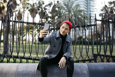 Spain, Barcelona, portrait of young man taking selfie with cell phone - JRFF02490