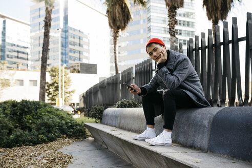 Spain, Barcelona, portrait of young man with mobile phone outdoors - JRFF02493