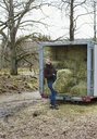Woman unloading hay bales from truck - FOLF09924