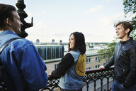 Friends laughing on a balcony in Stockholm, Sweden - FOLF09948