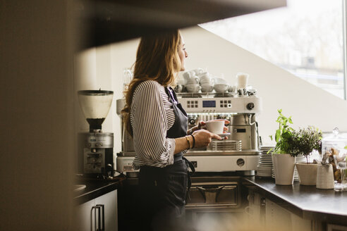 Barista holding coffee in cafe kitchen - FOLF10029