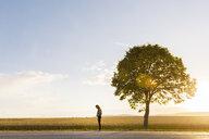 Teenage girl standing by tree in Vaderstad, Sweden - FOLF10164