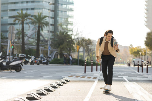 Man looking at cell phone while skateboarding in the city - VABF02081