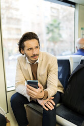 Portrait of man with smartphone in tram - VABF02087