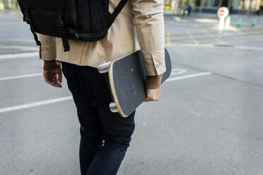 Man with backpack and skateboard in the city, partial view - VABF02090