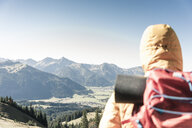 Austria, Tyrol, rear view of man on a hiking trip in the mountains enjoying the view - UUF16344
