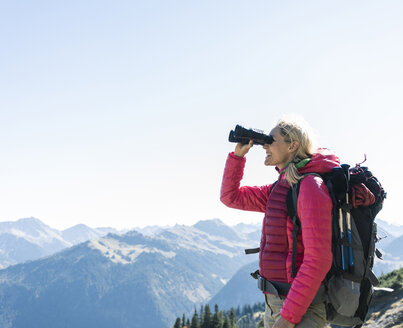Austria, Tyrol, happy woman looking through binoculars during hiking trip - UUF16347