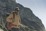 Austria, Tyrol, smiling man with sunglasses hiking in the mountains - UUF16353